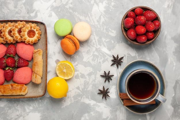 Vue de dessus de délicieux bagels avec des gâteaux, du thé aux fraises fraîches et des biscuits sur un bureau blanc