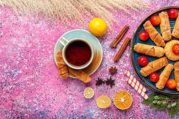 Vue de dessus de délicieux bagels sucrés à l'intérieur du plateau avec des prunes aigres et du thé sur une surface rose clair