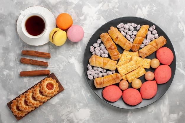Vue de dessus de délicieux bagels sucrés avec des macarons de biscuits craquelins et une tasse de thé sur un bureau blanc clair