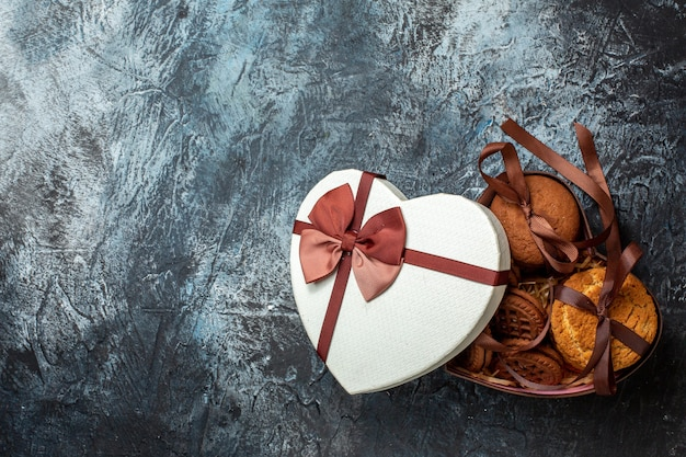 Vue de dessus de délicieux biscuits attachés avec des biscuits en corde dans une boîte en forme de coeur avec couvercle sur un espace libre de table gris