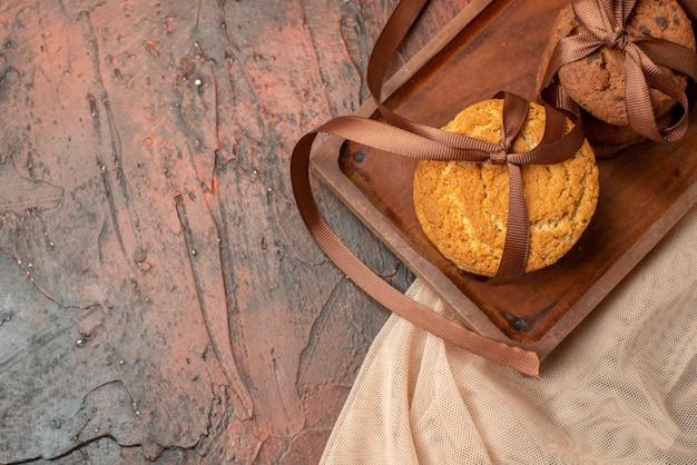 Vue de dessus de délicieux biscuits attachés avec une corde sur une planche de bois sur un espace libre de table rouge foncé