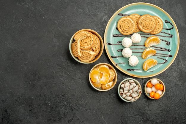Vue de dessus délicieux biscuits au sucre avec des bonbons sur fond gris foncé