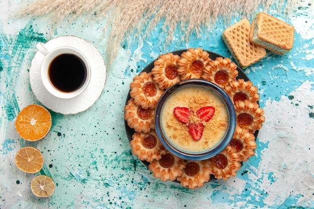 Vue de dessus de délicieux biscuits au sucre avec gaufres tasse de café et dessert aux fraises sur le bureau bleu