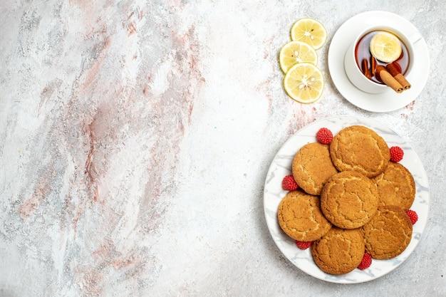Vue de dessus de délicieux biscuits au sucre avec une tasse de thé sur une surface blanche