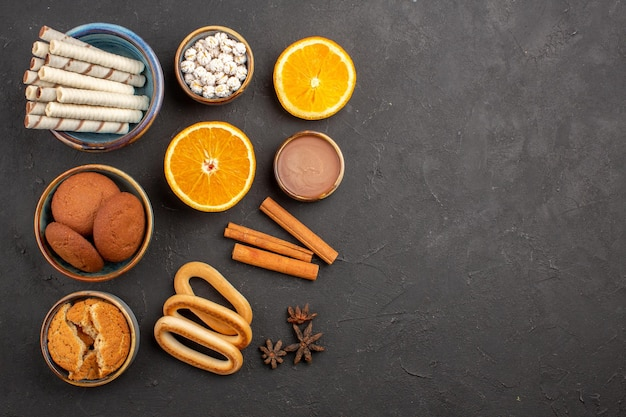 Vue de dessus de délicieux biscuits au sucre avec des tranches d'oranges sur fond sombre biscuit au thé au sucre biscuit aux fruits sucrés