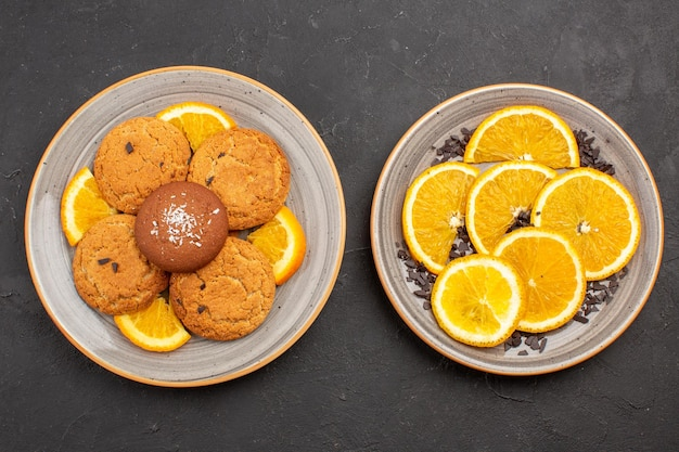 Vue de dessus de délicieux biscuits au sucre avec des tranches d'oranges fraîches sur fond sombre biscuit au sucre biscuit sucré aux fruits