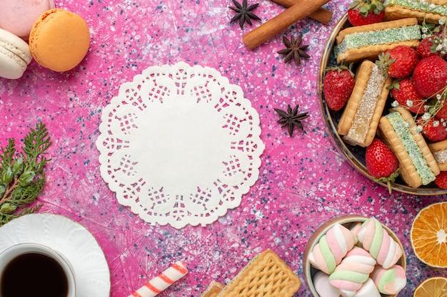 Vue de dessus de délicieux biscuits gaufres avec des fraises rouges fraîches et une tasse de thé sur une surface rose
