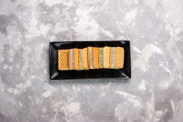 Vue de dessus de délicieux biscuits gaufres à l'intérieur du moule à gâteau noir sur une surface blanche