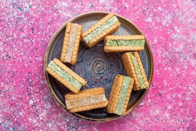 Vue de dessus de délicieux biscuits gaufres à l'intérieur de la plaque sur la surface rose
