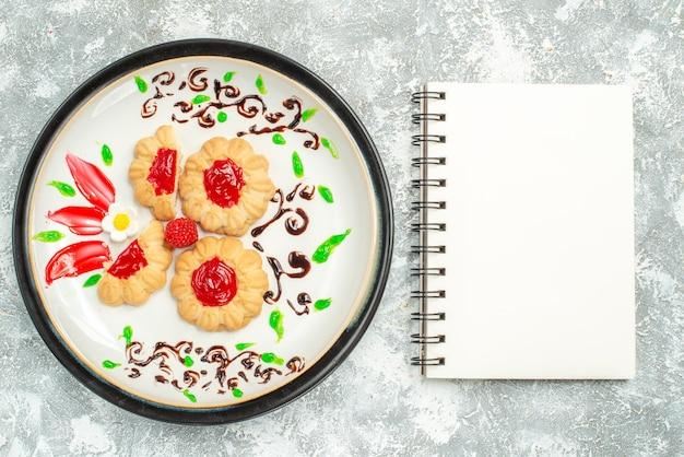 Vue de dessus de délicieux biscuits avec de la gelée rouge à l'intérieur de la plaque sur fond blanc clair biscuit de gâteau au sucre thé sucré