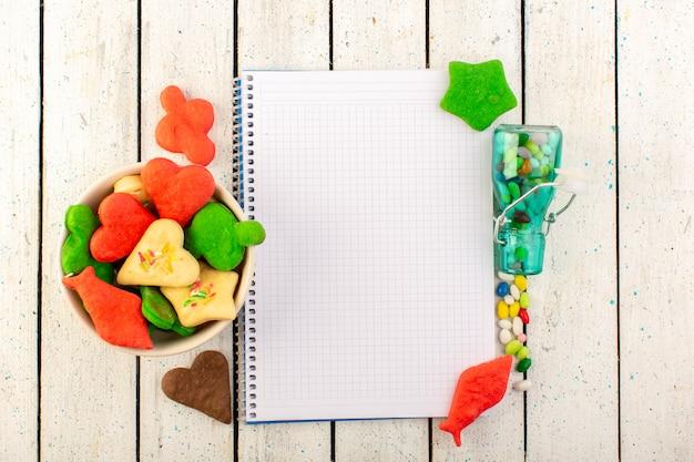Une vue de dessus de délicieux biscuits multicolores formés avec un cahier ouvert et des bonbons