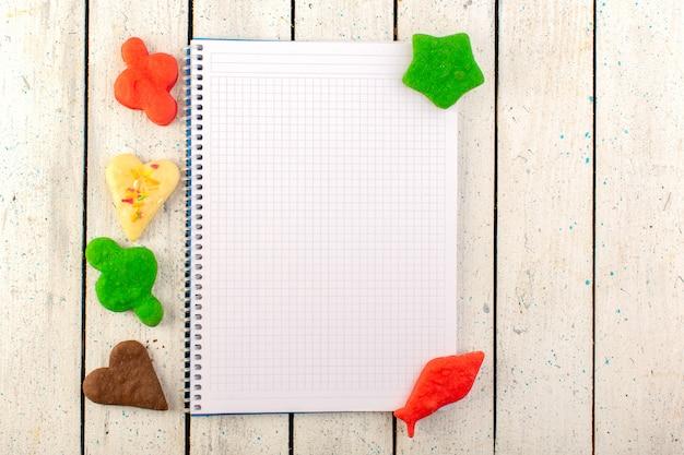 Une vue de dessus de délicieux biscuits multicolores formés avec un cahier ouvert