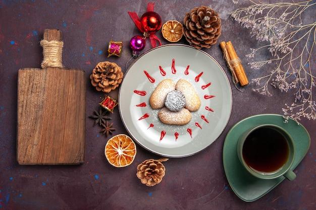 Vue de dessus de délicieux biscuits en poudre de sucre avec une tasse de thé sur fond noir