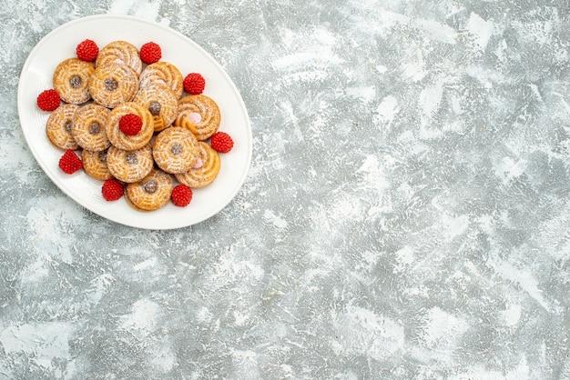Vue de dessus de délicieux biscuits ronds avec des confitures de framboises sur un espace blanc