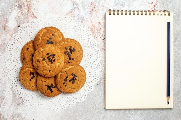Vue de dessus de délicieux biscuits de sable bonbons parfaits pour une tasse de thé sur une surface blanche
