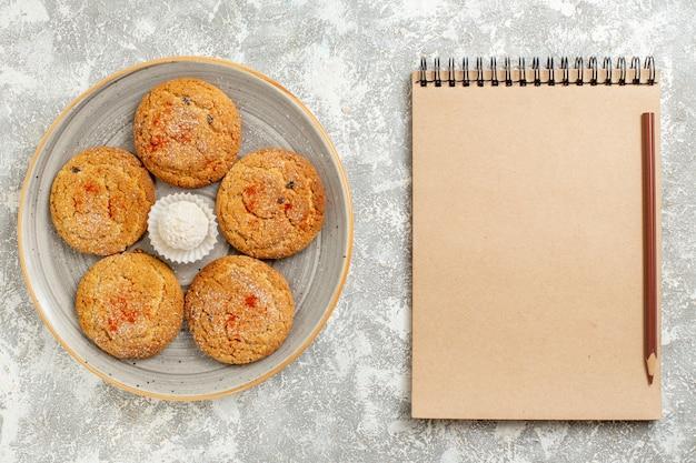 Vue de dessus de délicieux biscuits de sable à l'intérieur de la plaque sur un bureau blanc