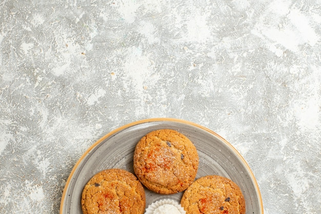 Vue de dessus de délicieux biscuits de sable à l'intérieur de la plaque sur fond blanc