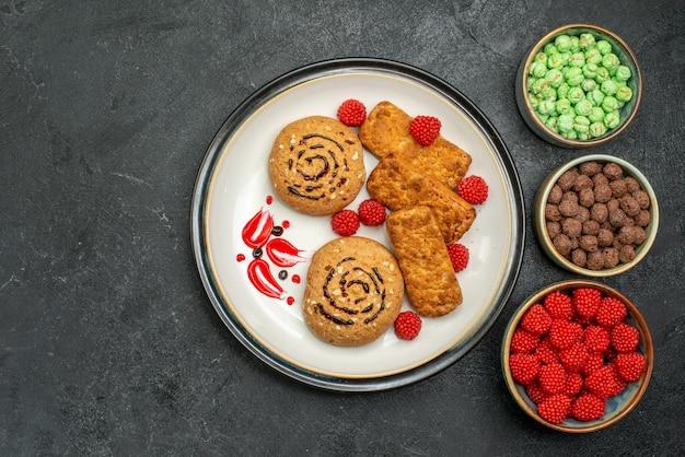 Vue de dessus délicieux biscuits sucrés avec d'autres bonbons sucrés sur fond gris biscuit gâteau au sucre sucré cookie thé
