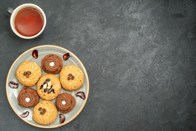 Vue de dessus de délicieux biscuits sucrés délicieux bonbons pour le thé sur l'espace gris