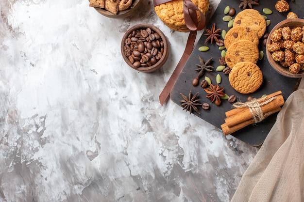 Vue de dessus de délicieux biscuits sucrés avec des graines de café et une tasse de café sur la table lumineuse