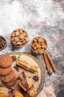 Vue de dessus de délicieux biscuits sucrés avec une tasse de café sur la table lumineuse