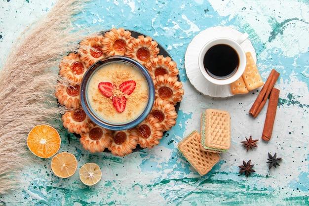 Vue de dessus de délicieux biscuits avec une tasse de confiture de café et un dessert aux fraises sur une surface bleu clair