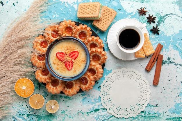 Vue de dessus de délicieux biscuits avec une tasse de confiture de café et un dessert aux fraises sur la surface bleue