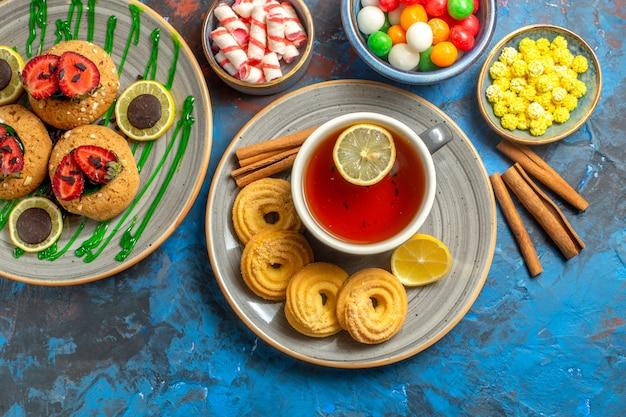 Vue de dessus de délicieux biscuits avec une tasse de thé et des bonbons sur le fruit sucré du cookie bleu