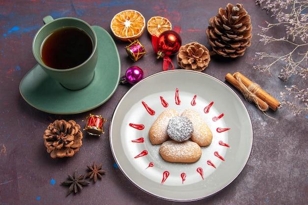 Vue de dessus de délicieux biscuits avec une tasse de thé sur fond noir