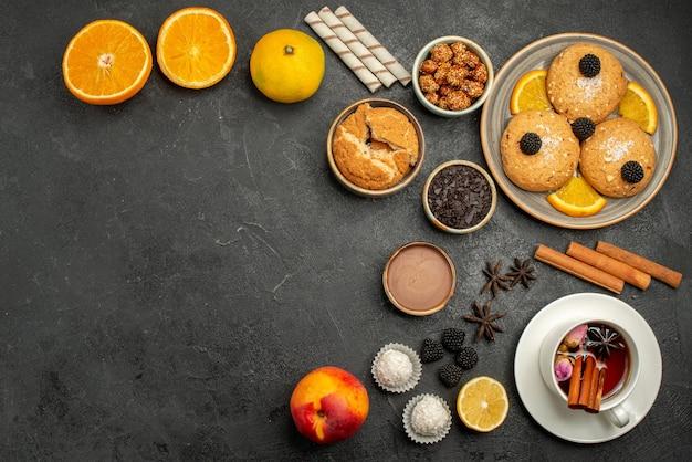 Vue de dessus de délicieux biscuits avec une tasse de thé sur un gâteau aux biscuits aux biscuits au thé noir