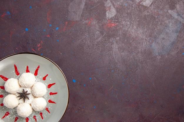 Vue de dessus de délicieux bonbons à la noix de coco avec glaçages rouges sur fond noir
