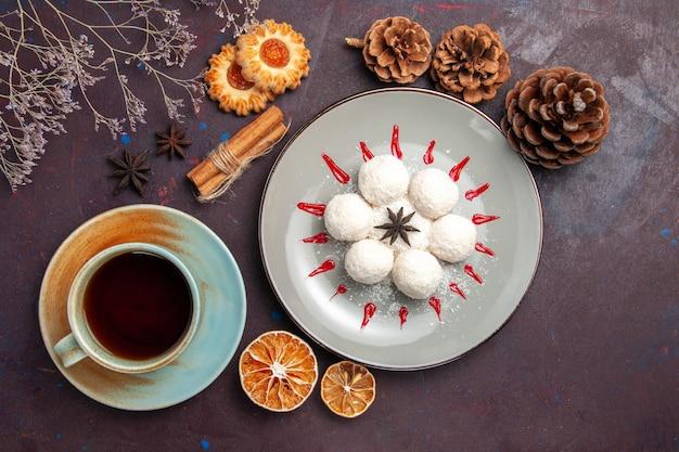 Vue de dessus de délicieux bonbons à la noix de coco petits et ronds formés avec une tasse de thé sur le fond sombre des bonbons à la noix de coco et des biscuits au gâteau sucré