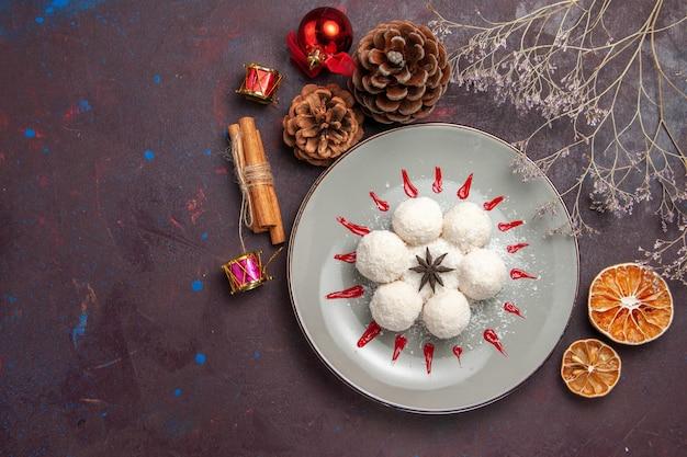 Vue de dessus de délicieux bonbons à la noix de coco ronds formés avec des glaçages rouges sur fond noir