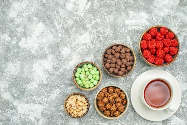 Vue de dessus de délicieux bonbons sucrés avec des noix et une tasse de thé sur un espace blanc