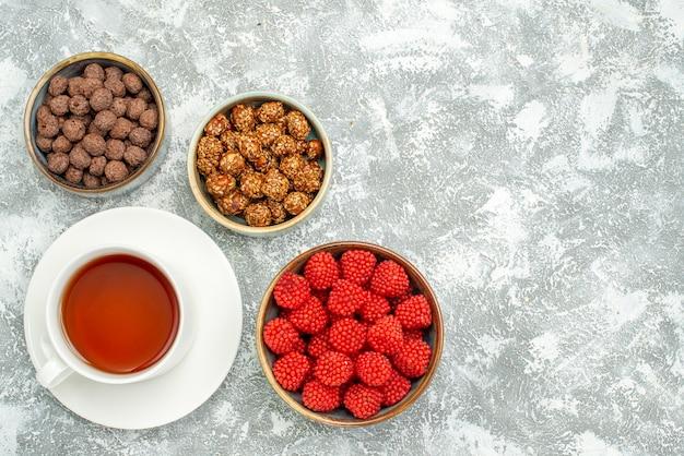 Vue de dessus de délicieux bonbons sucrés avec une tasse de thé sur un espace blanc