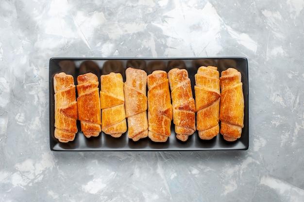 Vue de dessus de délicieux bracelets cuits à l'intérieur de la moisissure noire sur blanc, pâtisserie cuire au four gâteau aux biscuits sucré