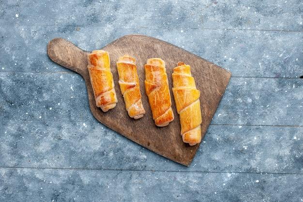 Vue de dessus de délicieux bracelets avec garniture sur le fond en bois gris pâtisserie au sucre sucré