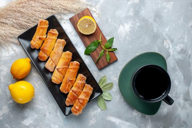 Vue de dessus de délicieux bracelets sucrés avec du citron et du thé sur une table lumineuse, un gâteau pâtissier cuire du sucre sucré