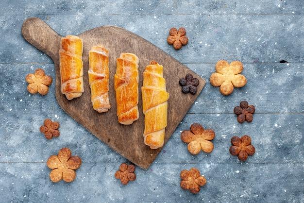 Vue de dessus de délicieux bracelets sucrés avec remplissage avec des biscuits sur le fond en bois gris pâtisserie au sucre sucré
