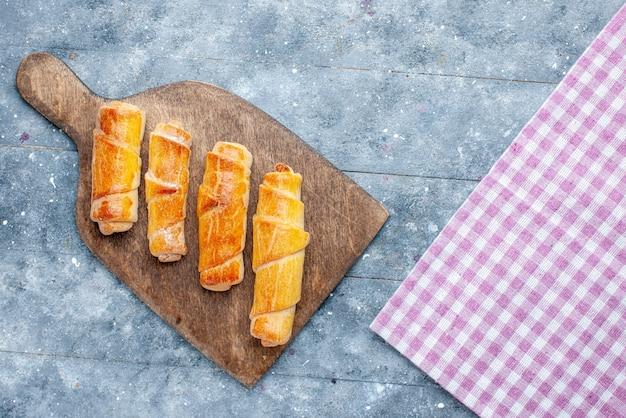 Vue de dessus de délicieux bracelets sucrés avec remplissage sur le fond en bois gris sucre sucré cuire au four biscuit biscuit
