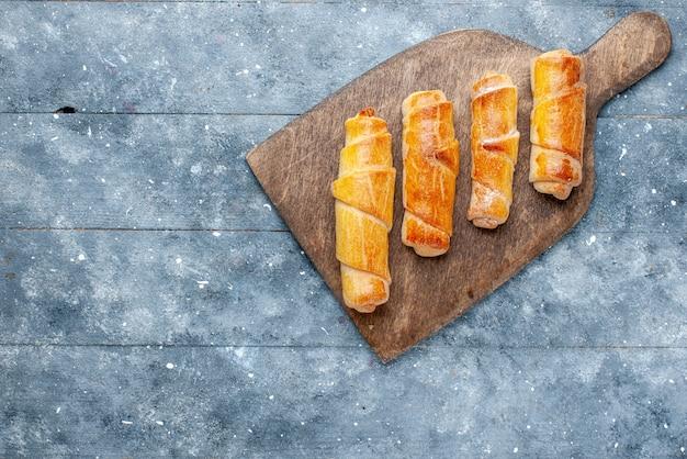 Vue de dessus de délicieux bracelets sucrés avec remplissage sur le fond gris pâtisserie au sucre sucré
