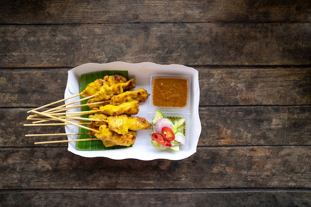 Vue de dessus de délicieux brochettes de satay de porc avec sauce trempette aux arachides dans un plateau de papier blanc sur woo