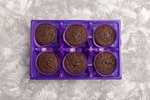 Vue de dessus de délicieux brownies au chocolat à l'intérieur de l'emballage violet sur le fond clair au chocolat pâte sucrée