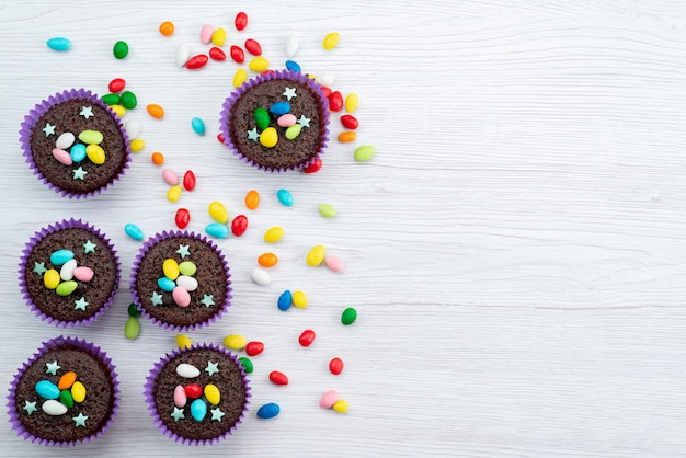 Une vue de dessus de délicieux brownies à l'intérieur des formes violettes avec des bonbons colorés sur blanc, bonbons de couleur bonbon
