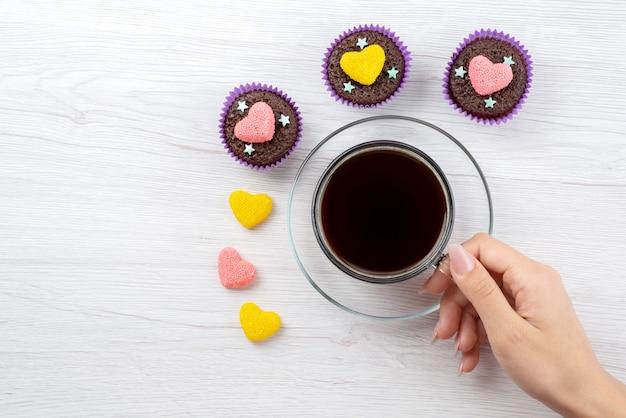 Une vue de dessus de délicieux brownies à l'intérieur des formes violettes avec une tasse de thé sur des bonbons de couleur blanc, bonbons