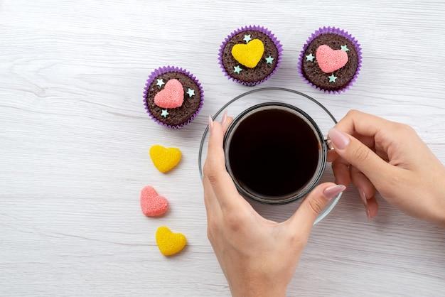 Une vue de dessus de délicieux brownies à l'intérieur des formes violettes avec tasse de thé tenant par femme sur blanc, bonbons de couleur bonbon