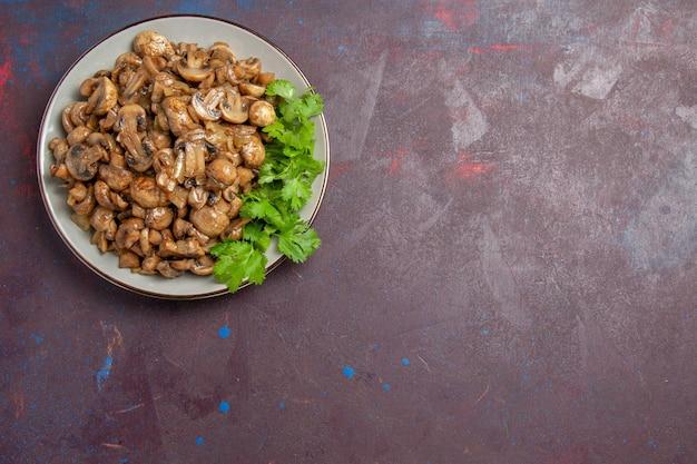 Vue de dessus de délicieux champignons cuits avec des légumes verts sur le plat de repas de fond sombre dîner nourriture végétale sauvage