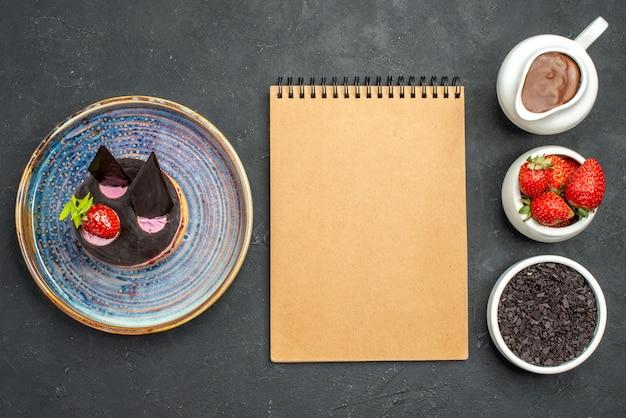 Vue de dessus délicieux cheesecake à la fraise et au chocolat sur des bols en assiette sur fond sombre isolé