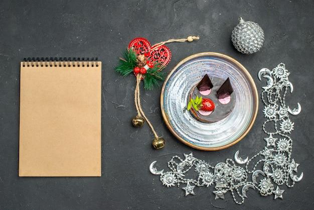 Vue de dessus délicieux cheesecake à la fraise et au chocolat sur une plaque d'argent ovale ornements de noël un cahier sur fond sombre isolé