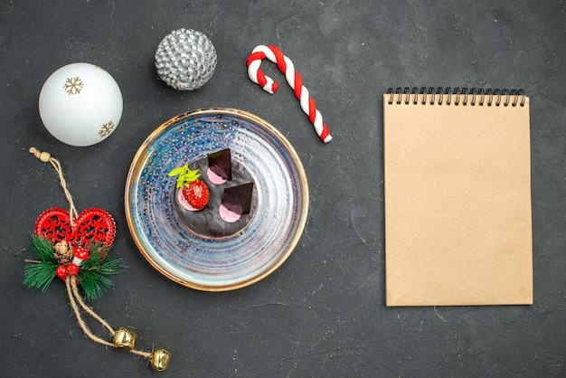 Vue de dessus délicieux cheesecake avec fraise et chocolat sur plaque ovale arbre de noël jouets un cahier sur fond sombre isolé